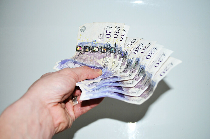 Hand holding £180 in £20 notes fanned out